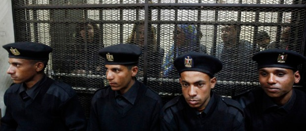 Some of the fourteen Egyptian activists stand in a cage during the opening of their trial in Cairo