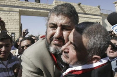 Muslim Brotherhood's Khayrat el-Shater hugs Hassan Malek after both were released from prison. (AP)