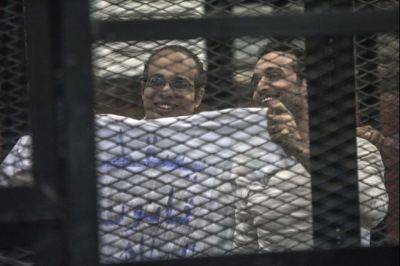 Political activist and coordinator of the April 6 Movement, Ahmed Maher and activist Ahmed Doma (R) show a T-shirt reading 'Dropping the law on demonstrations' during his trial on Dec. 8, 2013 in Cairo, Egypt. (Mahmoud Khaled/AFP/Getty Images)