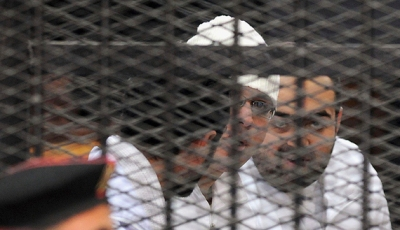 Political activists Ahmed Maher, Ahmed Douma (L) and Mohamed Adel (R) of the April 6 Youth Movement look on from behind bars in Abdeen court in Cairo, Dec. 22, 2013.  (photo by REUTERS)